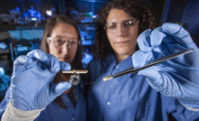 Heather Enright (left) and Anna Belle hold the brain-on-a-chip device and a microelectrode array.