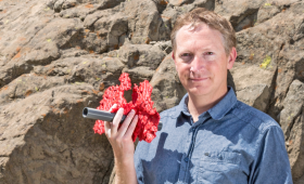 Joe Morris holding a 3D printed model of rock fractures