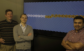 Three scientists in front of a crystalline material simulation image