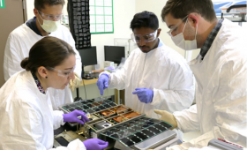 Engineers work on a cubesat.