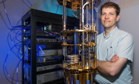 Jonathan DuBois standing next to a quantum computer