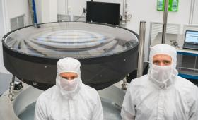 Large lens with two people in protective suits