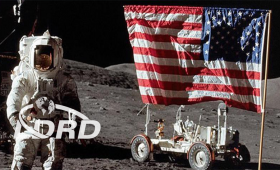 Astronaut next to American flag and rover on surface of moon