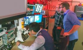 Three scientists looking at Movie Mode Dynamic Transmission Electron Microscope