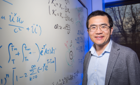 Yuan Shi standing by white board with algorithms