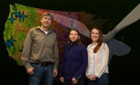Three researchers in front of U.S. map and turbine